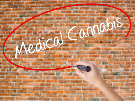 Woman Hand Writing Medical Cannabis with black marker on visual screen. Isolated on bricks. Business concept. Stock Photo