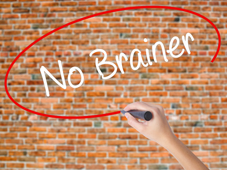 Woman Hand Writing No Brainer with black marker on visual screen. Isolated on bricks. Business, technology, internet concept. Stock Photo
