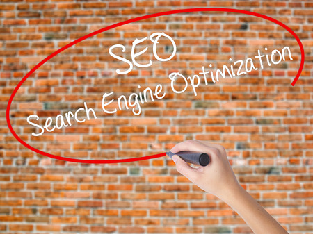 Woman Hand Writing SEO Search Engine Optimization with black marker on visual screen. Isolated on bricks. Business concept. Stock Photo