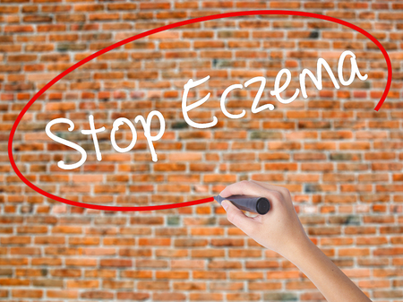 Woman Hand Writing Stop Eczema with black marker on visual screen. Isolated on bricks. Business concept. Stock Photo