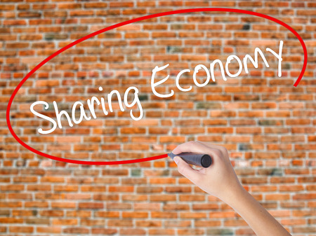 Woman Hand Writing Sharing Economy with black marker on visual screen. Isolated on bricks. Business concept. Stock Photo Stock Photo