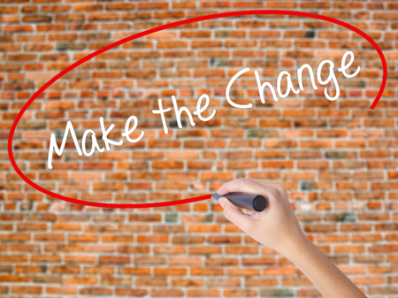 challenges ahead: Woman Hand Writing Make the Change with black marker on visual screen. Isolated on bricks. Business concept. Stock Photo