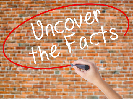 uncover: Woman Hand Writing Uncover the Facts with black marker on visual screen. Isolated on bricks. Business concept. Stock Photo Stock Photo