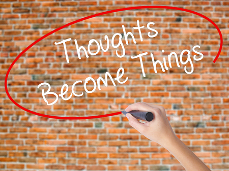 Woman Hand Writing Thoughts Become Things with black marker on visual screen. Isolated on bricks. Business concept. Stock Photo