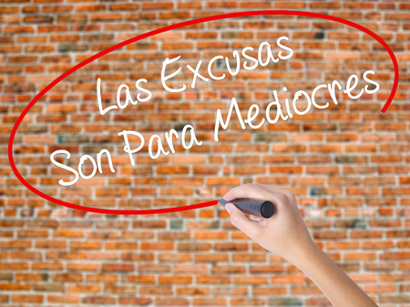 persevere: Woman Hand Writing Las Excusas Son Para Mediocres (Excuses are for Average People in Spanish) with marker on visual screen. Isolated on bricks. Business concept. Stock Photo