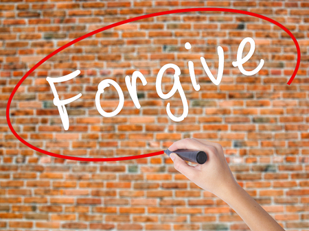 Woman Hand Writing Forgive with black marker on visual screen. Isolated on bricks. Business concept. Stock Photo