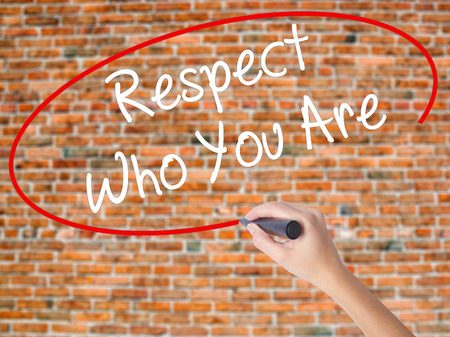 Woman Hand Writing Respect Who You Are with black marker on visual screen. Isolated on bricks. Business concept. Stock Photo