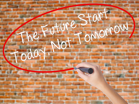 Woman Hand Writing The Future Start Today, Not Tomorrow with black marker on visual screen. Isolated on bricks. Business concept. Stock Photo