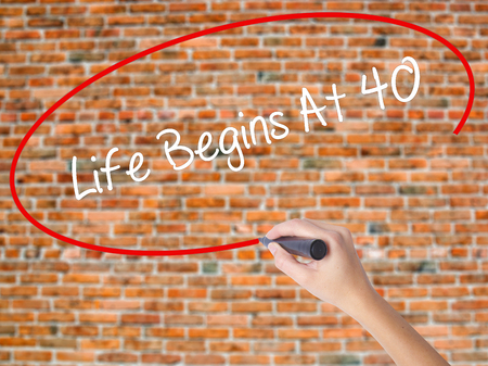 Woman Hand Writing Life Begins At 40  with black marker on visual screen. Isolated on bricks. Business concept. Stock Photo