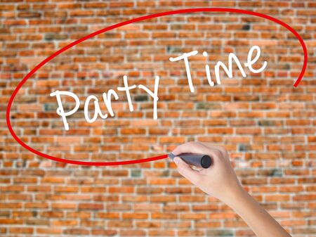 Woman Hand Writing Party Time with black marker on visual screen. Isolated on bricks. Business concept. Stock Photo Stock Photo