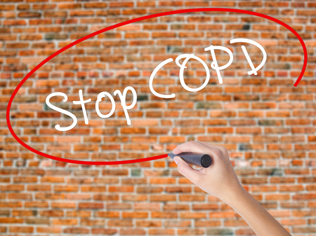 Woman Hand Writing Stop COPD with black marker on visual screen. Isolated on bricks. Business concept. Stock Photo