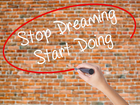 Woman Hand Writing Stop Dreaming Start Doing  with black marker on visual screen. Isolated on bricks. Business, technology, internet concept. Stock Photo