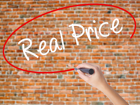 Woman Hand Writing Real Price with black marker on visual screen. Isolated on bricks. Business concept. Stock Photo