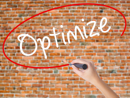 Woman Hand Writing Optimize with black marker on visual screen. Isolated on bricks. Business concept. Stock Photo Stock Photo