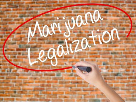 Woman Hand Writing Marijuana Legalization with black marker on visual screen. Isolated on bricks. Live, technology, internet concept. Stock Photo Stock Photo
