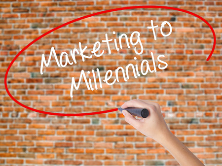Woman Hand Writing Marketing to Millennials with black marker on visual screen. Isolated on bricks. Business, technology, internet concept. Stock Photo Stock Photo
