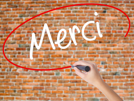 Woman Hand Writing Merci  (Thank You In French) with black marker on visual screen. Isolated on bricks. Business concept. Stock Photo