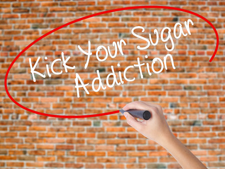Woman Hand Writing Kick Your Sugar Addiction with black marker on visual screen. Isolated on bricks. Business concept. Stock Photo