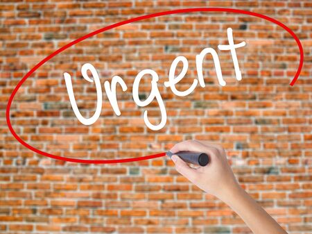 Woman Hand Writing Urgent  with black marker on visual screen. Isolated on bricks. Business, technology, internet concept. Stock  Photo