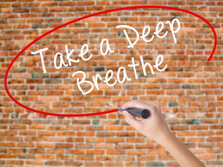 positiveness: Woman Hand Writing Take a Deep Breathe with black marker on visual screen. Isolated on bricks. Business concept. Stock Photo Stock Photo