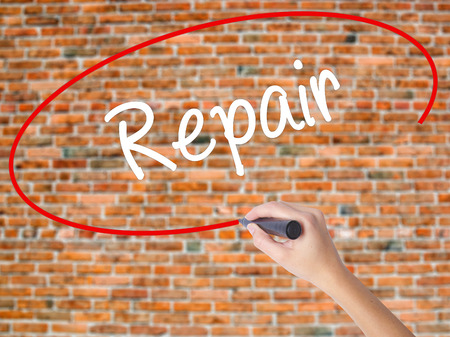 Woman Hand Writing Repair with black marker on visual screen. Isolated on bricks. Business concept. Stock Photo