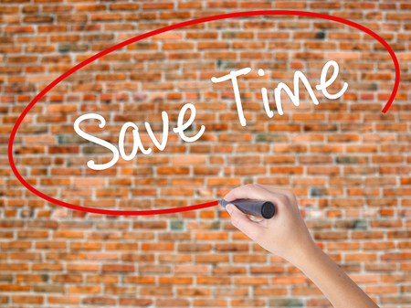Woman Hand Writing Save Time with black marker on visual screen. Isolated on bricks. Business concept. Stock Photo