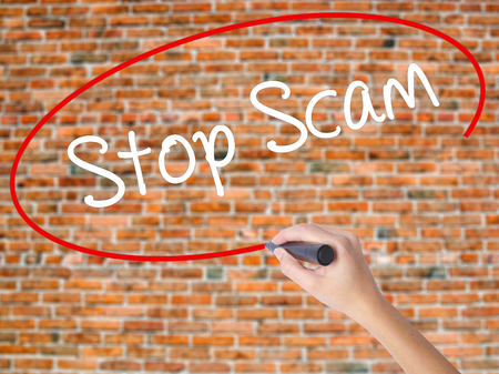 Woman Hand Writing Stop Scam with black marker on visual screen. Isolated on bricks. Business concept. Stock Photo