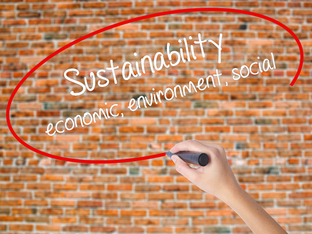 Woman Hand Writing Sustainability  economic, environment, social with black marker on visual screen. Isolated on bricks. Business, technology, internet concept.