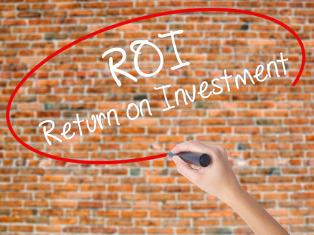 Woman Hand Writing ROI  Return on Investment with black marker on visual screen. Isolated on bricks. Business concept. Stock Photo Stock Photo