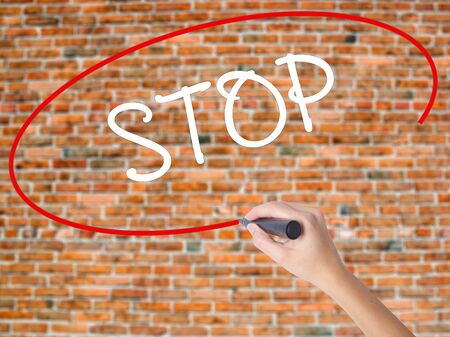 cyber terrorism: Woman Hand Writing STOP  with black marker on visual screen. Isolated on bricks. Business concept. Stock Photo