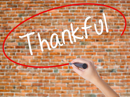 obliged: Woman Hand Writing Thankful  with black marker on visual screen. Isolated on bricks. Business concept. Stock Photo Stock Photo
