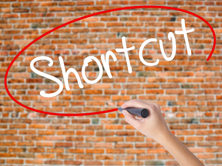 Woman Hand Writing Shortcut with black marker on visual screen. Isolated on bricks. Business concept. Stock Photo Stock Photo