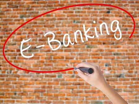 Woman Hand Writing E-Banking with black marker on visual screen. Isolated on bricks. Business concept. Stock Photo