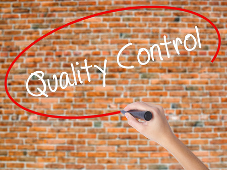 Woman Hand Writing Quality Control with black marker on visual screen. Isolated on bricks. Business concept. Stock Photo
