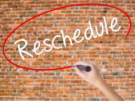 Woman Hand Writing Reschedule  with black marker on visual screen. Isolated on bricks. Business concept. Stock Photo