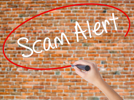 Woman Hand Writing Scam Alert  with black marker on visual screen. Isolated on bricks. Business concept. Stock Photo Stock Photo