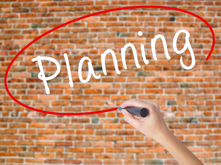 Woman Hand Writing Planning with black marker on visual screen. Isolated on bricks. Business concept. Stock Photo