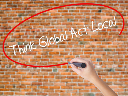 Woman Hand Writing Think Global Act Local with black marker on visual screen. Isolated on bricks. Business concept. Stock Photo
