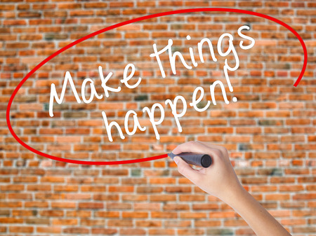 Woman Hand Writing Make Things Happen with marker on transparent wipe board. Isolated on bricks. Business, internet, technology concept. Stock Photo