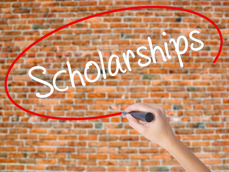 Woman Hand Writing Scholarships with black marker on visual screen. Isolated on bricks. Business concept. Stock Photo Stock Photo
