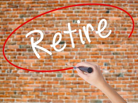 Woman Hand Writing Retire with black marker on visual screen. Isolated on bricks. Business concept. Stock Photo
