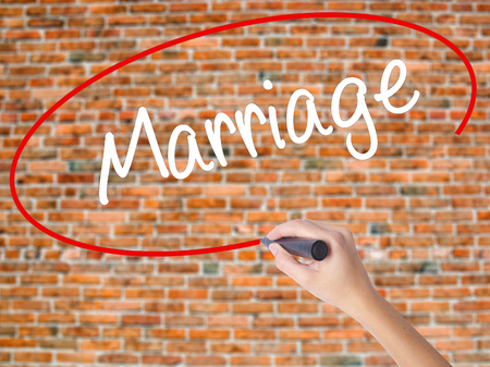 Woman Hand Writing Marriage with black marker on visual screen. Isolated on bricks. Business concept. Stock Photo