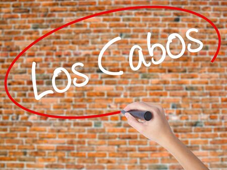 Woman Hand Writing Los Cabos with black marker on visual screen. Isolated on bricks. Business concept. Stock Photo