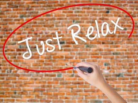 Woman Hand Writing Just Relax with black marker on visual screen. Isolated on bricks. Business concept. Stock Photo Stock Photo