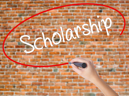Woman Hand Writing Scholarship with black marker on visual screen. Isolated on bricks. Business concept. Stock Photo