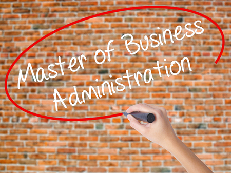Woman Hand Writing Master of Business Administration with black marker on visual screen. Isolated on bricks. Business concept. Stock Photo
