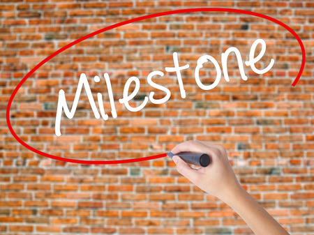 Woman Hand Writing Milestone with black marker on visual screen. Isolated on bricks. Business concept. Stock Photo Stock Photo