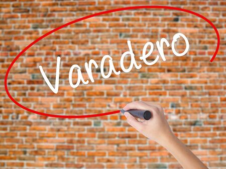 Woman Hand Writing Varadero  with black marker on visual screen. Isolated on bricks. Business concept. Stock Photo Stock Photo