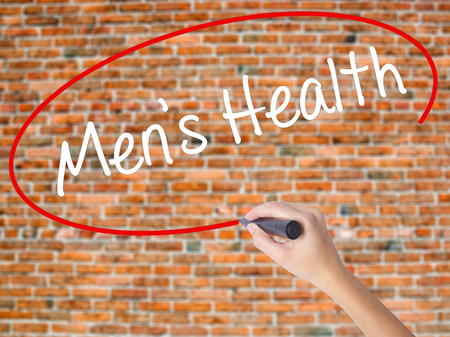 Woman Hand Writing Mens Health with black marker on visual screen. Isolated on bricks. Business concept. Stock Photo
