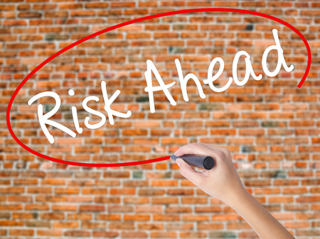 Woman Hand Writing Risk Ahead with black marker on visual screen. Isolated on bricks. Business concept. Stock Photo Stock Photo